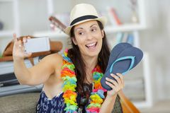 Female tourist with lei necklace taking selfie holding slippers royalty free stock photography