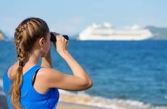 Female tourist looking through binoculars at white cruise ship stock image