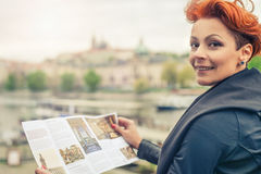 Female tourist looking at city guide. Female tourist standing near river and looking at city guide stock image