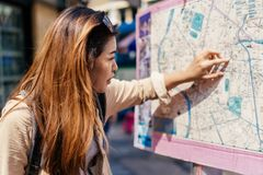 Female tourist looking at the city map while getting lost. Young female tourist woman looking at the city map and directions in confused looking in Bangkok stock image