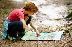 Female tourist looking on a map. In a forest royalty free stock photography