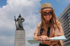 Female Tourist Looking at Map near Admiral Yi Sun-sin Monument at Gwanghwamun Square. Young Woman Exploring Historical Royalty Free Stock Photography