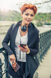 Female tourist looking at mobile phone. Young female tourist with headphones looking at mobile phone and holding city guide stock photography