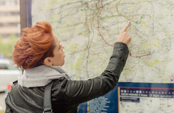 Female tourist looking at public street map. Female tourist looking at big public outdoor street map stock photo