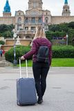 Female tourist with luggage. Blonde female tourist holding grey suitcase while admiring the National Museum of Arts in Barcelona, Catalonia - City break concept stock photos