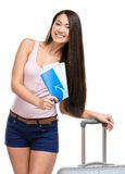 Female tourist with luggage and ticket. Half-length portrait of female tourist with travel suitcase and boarding pass, isolated on white royalty free stock image