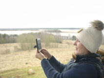 Female Tourist Photographer. Woman taking pictures on mobile phone while travel, outdoor selective focus shot Royalty Free Stock Images