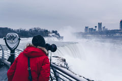 Female tourist photographing Niagara Falls in the winter. A woman in a red coat photographing Niagara Falls from the New York side Stock Photo