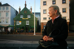 Female Tourist - Poole Quay. A female tourist enjoys the setting sun sitting on a quay wall at Poole harbour with the Poole Arms in the background.  Poole Arms Royalty Free Stock Photo