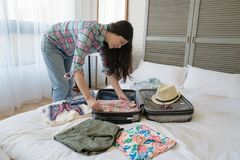 Female tourist preparing her suitcase. Side view of the Asian female tourist preparing her suitcase. She folded every clothes nice and neat royalty free stock image