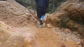 Female tourist in raincoat walking on stone mountain trail. Woman hiking through a narrow canyon. Girl in sneakers going stock footage