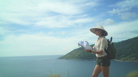 Female Tourist Reading Map At The Top Of The Hill. Young attractive woman with map of island, traveler come down to the end of the journey stock video footage