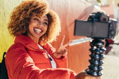 Female tourist recording content for her travel blog. Smiling afro american woman traveller taking a selfie using her digital camera. Smiling female tourist royalty free stock image