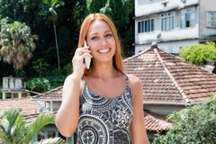 Female tourist with red hair talking with friend at phone royalty free stock image
