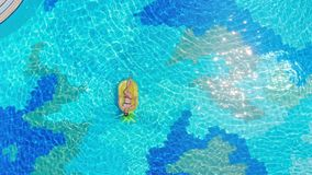 Female tourist relaxes in a pool, floating on a mattress.