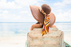 Female tourist relaxing in deck chair at beach in vacation Royalty Free Stock Photography