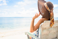 Female tourist relaxing in deck chair at beach in vacation Stock Photo