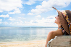 Female tourist relaxing in deck chair at beach in vacation Stock Photos