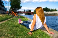 Female tourist relaxing in the grass, gazing at the boats passing under Moltke Bridge Moltkebrücke on Spree river. With her bike parked nearby, on a hot royalty free stock photos