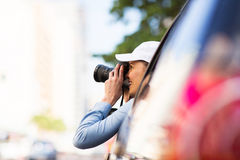 Female tourist road trip. Female tourist on road trip and taking photos outside of car window stock images