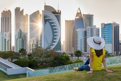 Female tourist sits in a park in front of the skyline of Doha, Qatar Royalty Free Stock Photos