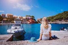 Female tourist sitting on the pier with blau sun hat laying behind. Assos village with beautiful traditional houses is. In front of sea bay. Kefalonia, Greece royalty free stock photos
