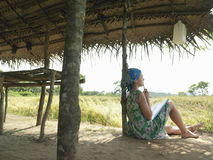 Female Tourist Sitting Under Hut Roof In Field Stock Photography