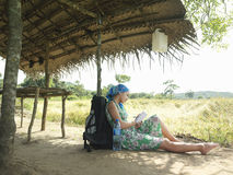 Female Tourist Sitting Under Hut Roof In Field Royalty Free Stock Photography