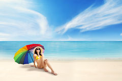 Female tourist sitting under umbrella Royalty Free Stock Photo
