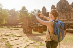Female tourist with smartphone in Angkor Thom, Cambodia Stock Image