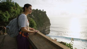 Female tourist standing on the top of mountain with breathtaking view of the ocean and cliff. Girl is looking at the stock footage