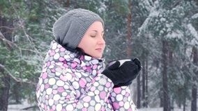 A female tourist stands against a winter forest or park on a snowy day and drinks hot tea from a cup. Close-up. stock footage