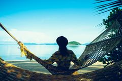 Female tourist swinging in hummock on tropical beach. Koh Mak Thailand royalty free stock photos