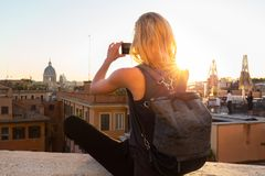 Female tourist taking mobile phone photo of Piazza di Spagna, landmark square with Spanish steps in Rome, Italy at Royalty Free Stock Photos