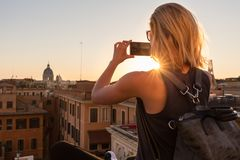 Female tourist taking mobile phone photo of Piazza di Spagna, landmark square with Spanish steps in Rome, Italy at Royalty Free Stock Photography