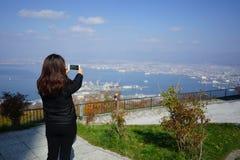 Female tourist taking phot of beautiful view of Hakodate town fr