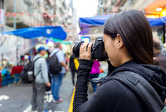 Female tourist taking photo with camera in street at Hong Kong Stock Images