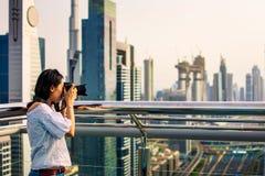 Female tourist taking photo of Dubai cityscape royalty free stock images