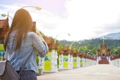 Female tourist taking picture of Buddhist temple in with mobile smart phone Royalty Free Stock Images