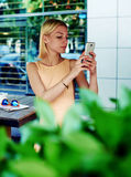 Female tourist taking picture with her smart phone while resting at coffee shop Royalty Free Stock Photos