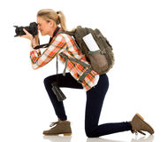 Female tourist taking pictures. Female tourist on her knee taking pictures royalty free stock photography