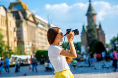 Female tourist in Timisoara. Female tourist photographing landmarks on the Victory square in Tmisoara city, Romania royalty free stock photos