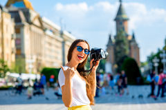 Female tourist in Timisoara. Female tourist photographing landmarks on the Victory square in Tmisoara city, Romania stock photos