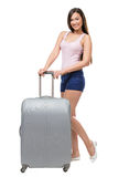 Female tourist with travel suitcase. Full-length portrait of female tourist with silver travel suitcase wearing shorts and T-shirt, isolated on white Royalty Free Stock Image