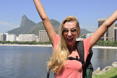 Female tourist traveling at Rio de Janeiro with Christ Redeemer. Blond young tourist female backpacker  traveling at Rio de Janeiro with the Christ Redeemer in Royalty Free Stock Photos