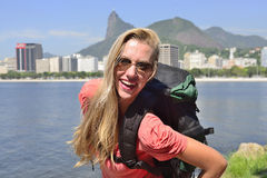 Female tourist traveling at Rio de Janeiro with Christ Redeemer. Blond young tourist female backpacker  traveling at Rio de Janeiro with the Christ Redeemer in Royalty Free Stock Image