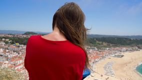 Female tourist using coin paid binoculars on high hill and looking at cityscape of Nazareth, Portugal stock video footage