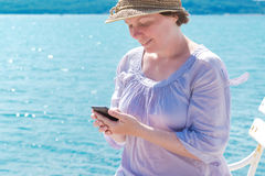 Female tourist using mobile phone at seaside on summer holiday Stock Images