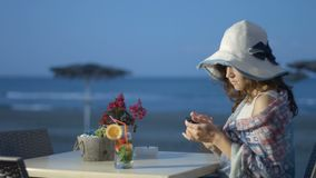 Female tourist using smartphone, typing message at beach cafe with sea view. Stock footage stock video