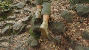 A female tourist is walking along a stony path, closeup legs